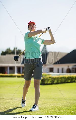 Full length of golfer woman taking shot while standing against clear sky