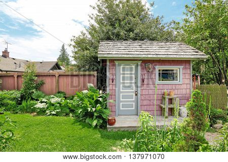 Home Garden On Backyard With Small Red Barn Shed