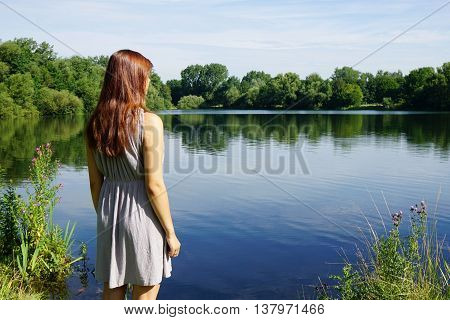 rear view of young woman looking over idyllic lake with copy space