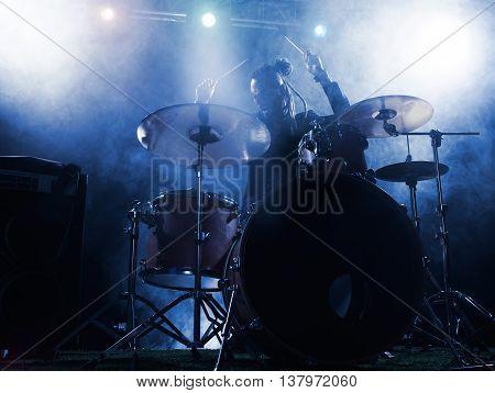 Silhouette of the drummer on stage. Dark background smoke spotlights