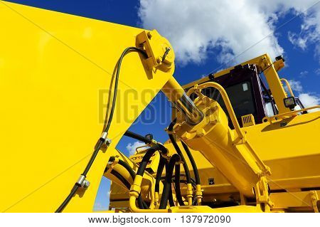 Bulldozer, huge yellow powerful construction machine with big bucket, focused on hydraulic piston arm, heavy industry, blue sky and white clouds on background