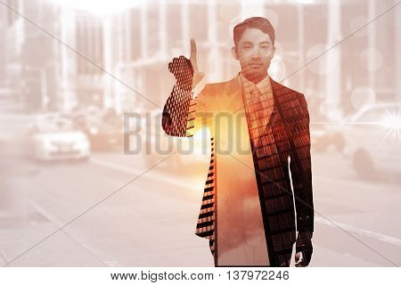 Stern asian businessman pointing against blurry new york street