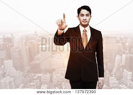 Stern asian businessman pointing against image of a city landscape