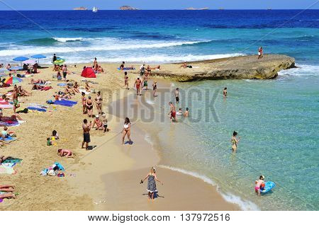 SAN ANTONIO, SPAIN - JUNE 15: Sunbathers at Cala Conta beach on June 15, 2015, in San Antonio, in Ibiza Island, Spain. Ibiza is a well-known summer tourist destination in Europe