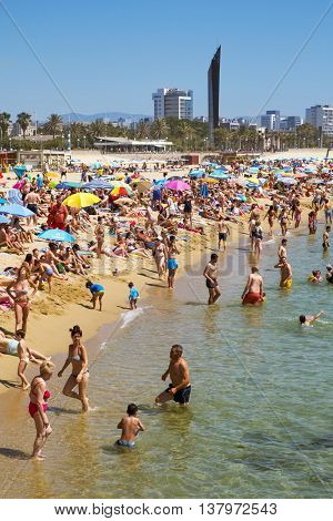 BARCELONA, SPAIN - JULY 10: People sunbathing at Platja del Bogatell beach on July 10, 2016 in Barcelona, Spain. This busy beach is mainly frequented by the locals