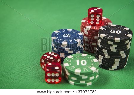 Gambling chips, red dice on green card table background