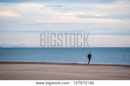 Valencia, Spain - JAN 6, 2016: Man running on the beach with the sea in the background