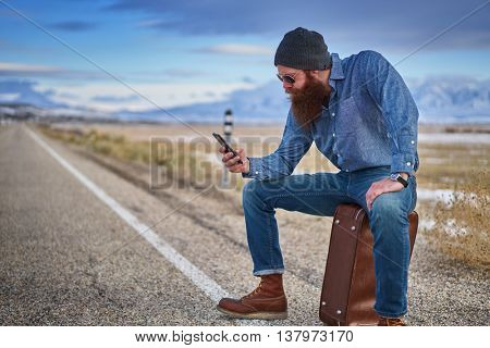 bearded hitch hiker sitting on suit case using smart phone