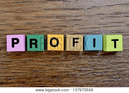 The word Profit on wooden table closeup