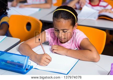 High angle view of girl writing on book in classroom
