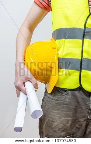 Worker With Yellow Helmet Holds Blueprints Or Documentation.