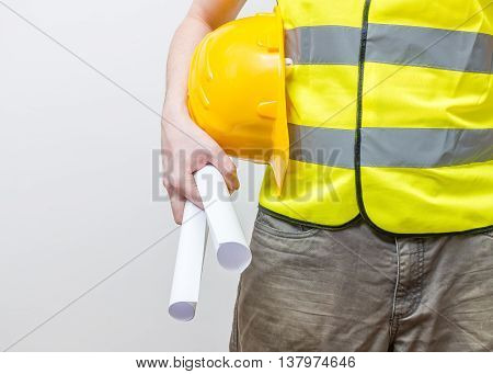 Worker with yellow helmet holds blueprints. Maintenance concept.