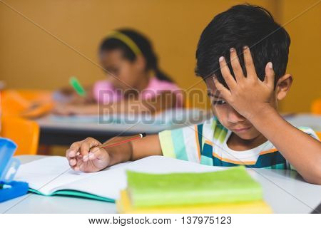 Irritated boy with head in hand looking at book on bench in classroom