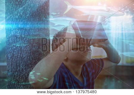 Fish swimming with shark in darkest water against elementary boy looking through virtual reality headset in school library