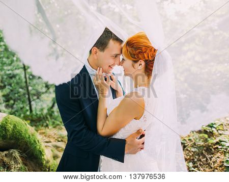 Happy young newly married couple holding hands and softly kissing under white veil in the green forest.