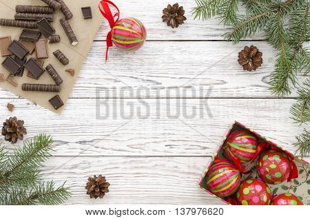 Christmas Card with chocolate candies christmas decorations and fir branches on white wooden background. Copy space composition.