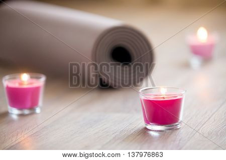 Lighted Pink Candle And Rolled Brown Yoga, Pilates Mat On The Floor. Close Up