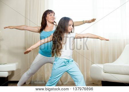 Pregnant Mother And Kid Girl Practicing Yoga At Home