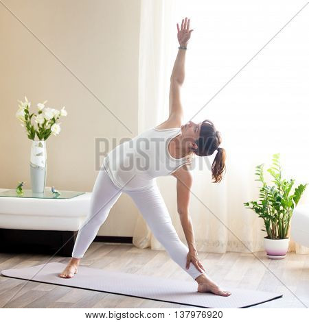 Pregnant Woman Doing Utthita Trikonasana Yoga Pose At Home
