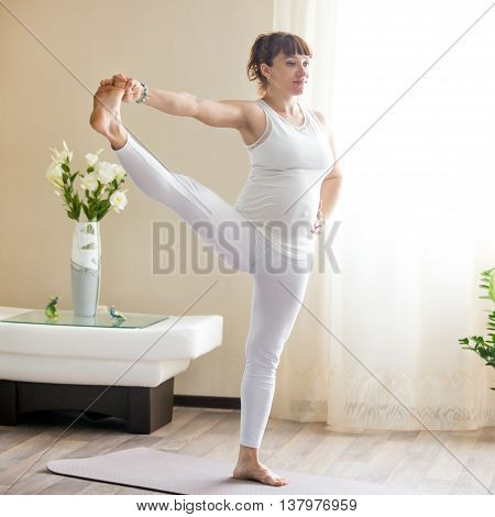 Pregnant Woman Doing Extended Hand To Big Toe Yoga Pose At Home