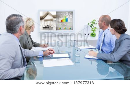Business team looking at time clock against energy efficient house graphic against a background