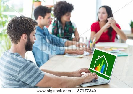Casual businessman typing on his laptop against energy efficient house graphic against a background