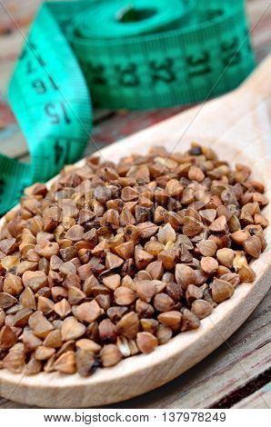 Buckwheat groats in a wooden spoon and centimeter