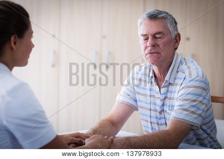 Female doctor consoling senior man at home