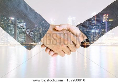 Double exposure of business men and women shaking hands with each other to work together.