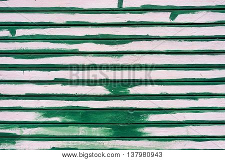 White wooden wall from boards partially painted green paint lines