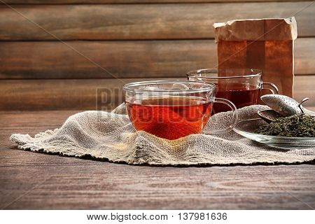 Glass cups of tea with hessian napkin on wooden background
