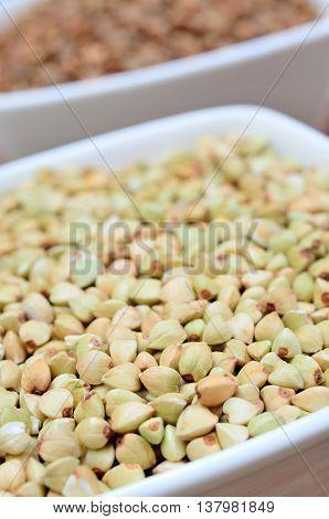 Bowl with buckwheat groats on background closeup