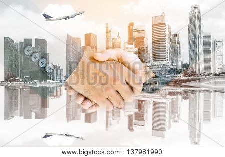 Double exposure handshake of business peoples with the airplane flying over the city background.