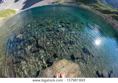 Fisheye View From Above Of Alpine Transparent Lake And Human Feet Into The Water, In Idyllic Unconta