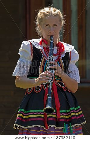 ROMANIA TIMISOARA - JULY 72016:Young singer girl at clarinet from Poland in traditional costume present at the folk festival
