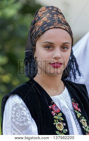 ROMANIA TIMISOARA - JULY 7 2016: Young woman from Romania in traditional costume present at the international folk festival