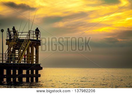 Coastal pier with silhouettes of anglers during sunset. Baltic Poland.