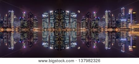 Panoramic view at night of  a megalopolis skyscrapers  with reflection  of Singapore city.