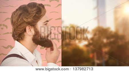 Profile view of hipster touching beard against composite image of mustaches