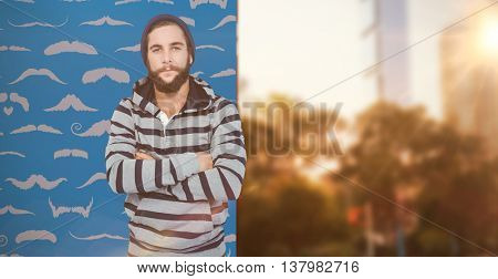 Portrait of hipster with hooded shirt against composite image of mustaches