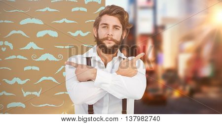 Confident hipster pointing sideways with arms crossed against composite image of mustaches