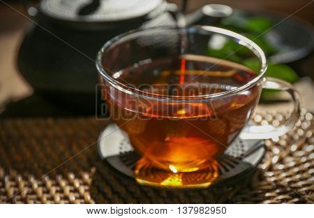 Traditional eastern tea ceremony with teapot and teacup on wicker mat