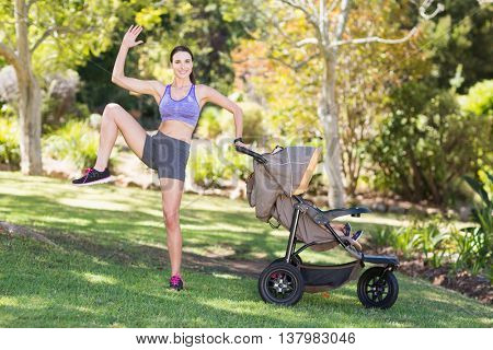 Young woman exercising with baby stroller in park