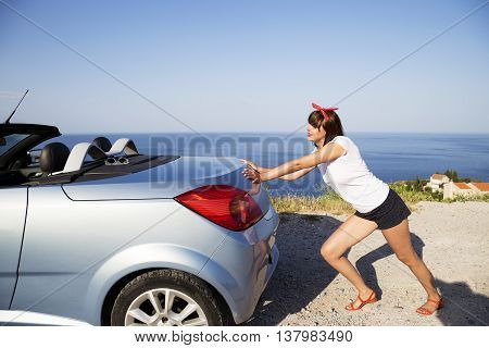 Young woman push the car runs out of gas.