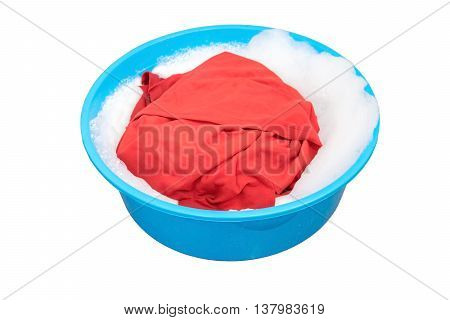 Red shirt soaked in washing powders in the plastic basin.