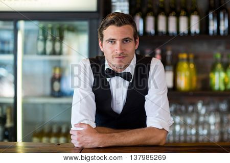 Portrait of confident bartender leaning on bar counter