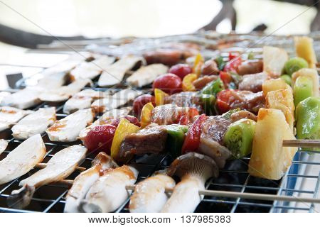 chicken shish kebab on bbq grill in sauce on skewers with tomatoes and peppers. shrimp and eringii mushroom grill.