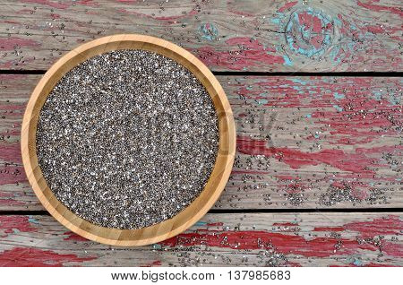 Bamboo bowl with chia seeds on rustic table