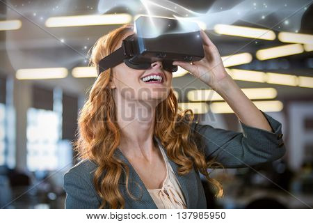 Abstract glowing black background against smiling businesswoman using virtual reality simulator