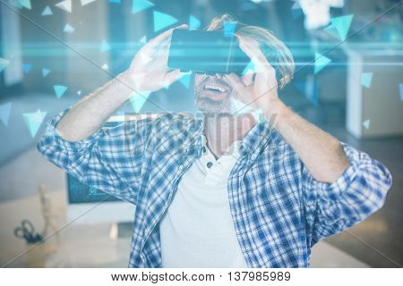 Technical screen with little pyramids against smiling businessman using virtual reality simulator